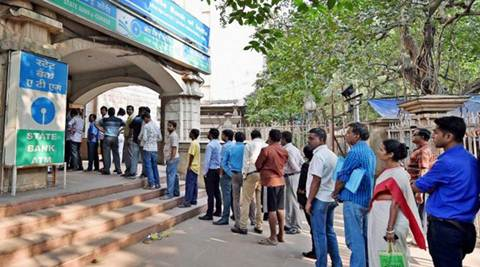 People queue as they wait for their turn to exchange or deposit their old high denomination banknotes outside a bank. (PTI)
