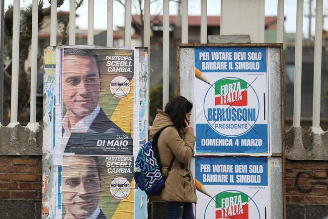 A woman walks past electoral posters of the 5 Star's candidate Luigi Di Maio and the Forza Italia party (Source: REUTERS)