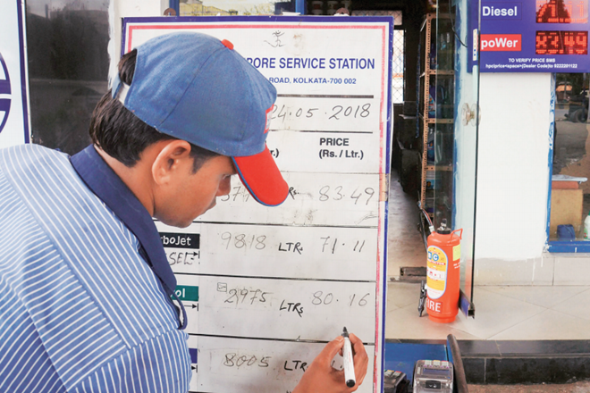 A petrol pump employee changes the prices on a board at a fuel station even as fuel prices record the highest-ever, in Kolkata, on Thursday