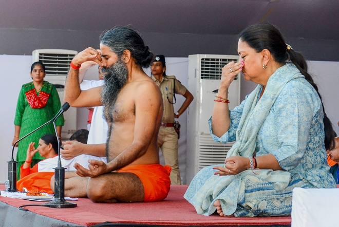 Yoga guru Ramdev Baba and Rajasthan Chief Minister Vasundhara Raje perform yoga during an event to set the Guinness World Record for 'The Largest Yoga Lesson' during the International Day of Yoga in Kota on Thursday.