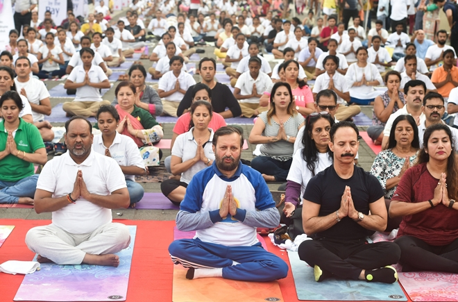 Union Human Resource Development Minister Prakash Javdekar performs yoga to mark the 4th International Day of Yoga in Mumbai on Thursday.